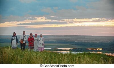 People in traditional russian folk clothes walking on the...