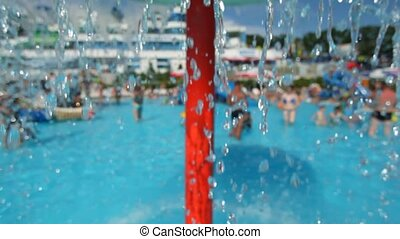 people in water park, focus on falling water in foreground
