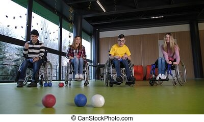 People in wheelchairs enjoying boccia game indoors