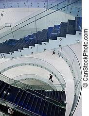 people inside a modern building (color toned image; motion blurred image)