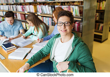 happy student boy reading books in library