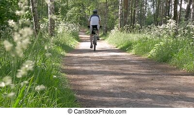 People lead a healthy lifestyle. A man is riding a bicycle in the park.