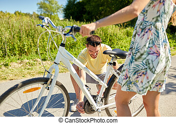 happy young couple fixing bicycle on country road