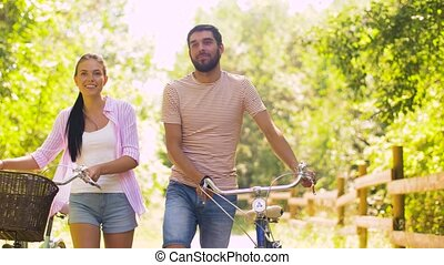 couple with bicycles walking along summer park