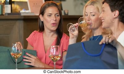women with shopping bags at wine bar or restaurant - people,...