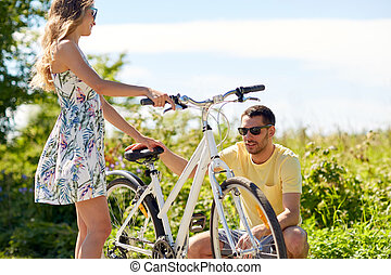 young couple fixing bicycle on country road