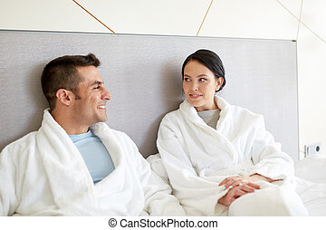 happy couple in bed at home or hotel room
