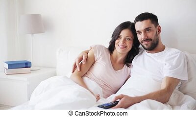 happy couple watching tv in bed at home