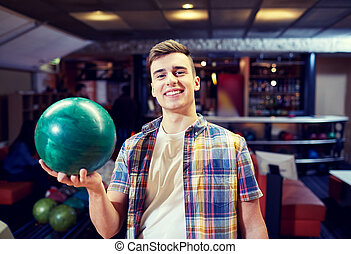 happy young man holding ball in bowling club