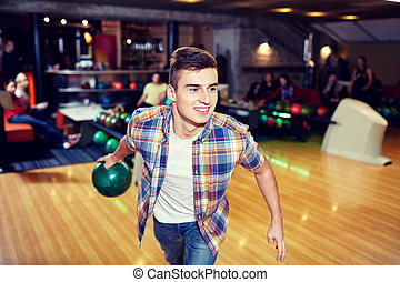 happy young man throwing ball in bowling club