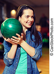 happy young woman holding ball in bowling club