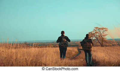 people lifestyle tourists travel in nature the autumn go on the road path adventure . slow motion video. two hiker with outdoor backpacks hiking. tourist concept the travel man tourism