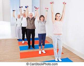 People Lifting Dumbbells At Gym