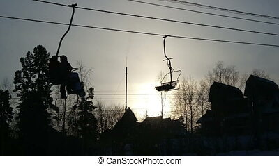 people lifting on the chair lift at ski resort in mountains