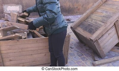 People load firewood in container