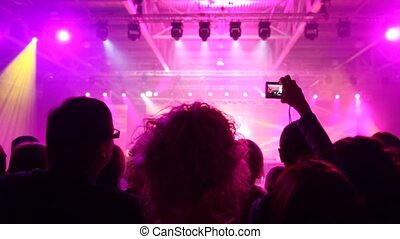 People look a concert of popular music and records it on camera