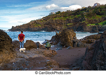 People looking at rocky beach in Seixal, Madeira