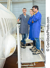 People looking at side of aircraft fuselage