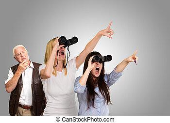 people looking through binoculars against a grey background