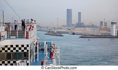 people looks from cruise ship moving past by Abu Dhabi with...