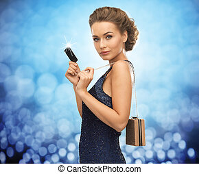 people, luxury, night life and finance concept - beautiful woman in evening dress with vip card and bag over blue lights background