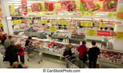 People make purchases at the store, the camera moves along the supermarket