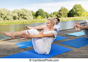 fitness, sport, yoga and healthy lifestyle concept - group of people making half-boat pose on mat outdoors on river or lake berth