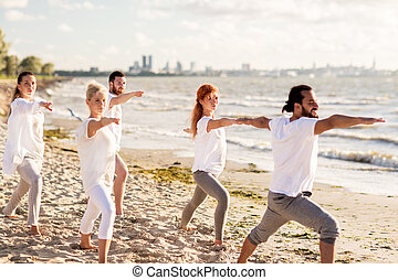 people making yoga in warrior pose on beach - fitness, sport...