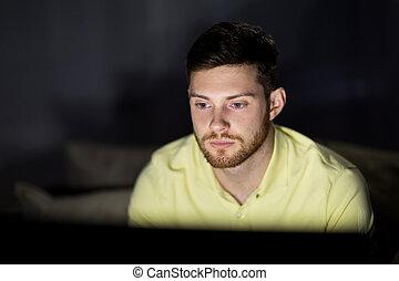 young man watching tv at night