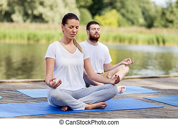 people meditating in yoga lotus pose outdoors - fitness,...
