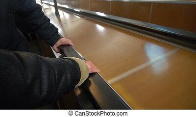 People move on an escalator,human hand on the railing.