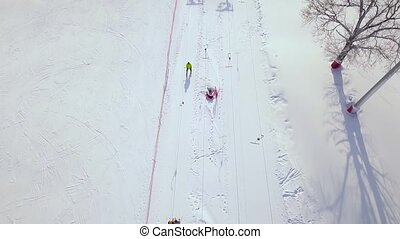 People moving on ski lift on snow slope in winter resort. Ski elevator on snow mountain for transportation skiers and snowboarders drone view.