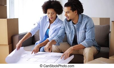 happy couple with blueprint and boxes at new home - people, ...