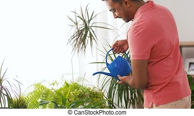indian man watering houseplants at home - people, nature and...