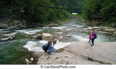 People near beautiful flowing water of river in green forest...