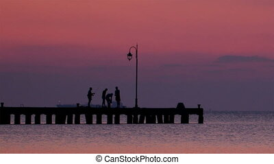 People on a pier at sunset