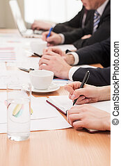 People on business meeting. Cropped image of people in formalwear working together while sitting in a row at the table