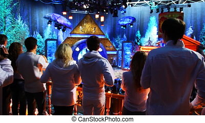 people on cell phones and cameraman to camera shoot in studio New Year show
