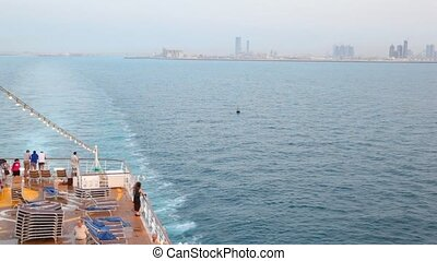 people on deck of cruise ship sailing out Abu Dhabi, capital of UAE