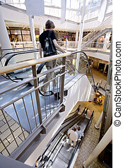 shopping center - People on escalators of a shopping center...