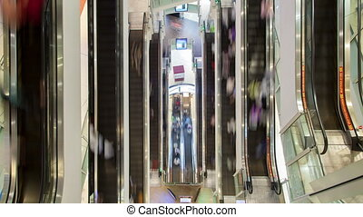 People on fast moving escalator in shopping mall time-lapse view from above