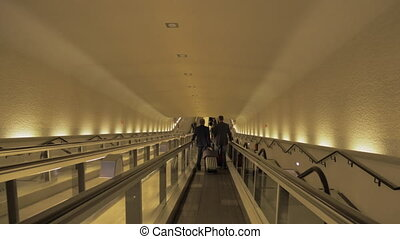 People on flat escalator at the airport in Paris, France