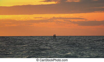people on kayak sail in ocean during sunset - People on ...