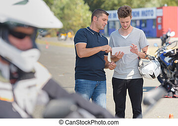 People on motorcycle training course looking at tablet