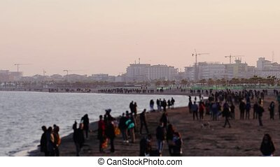 People spend time walking on ocean beach against park and construction site with cranes in autumn evening timelapse combined shot