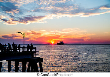 People on Pier Sillouetted with Freighter at Sunset