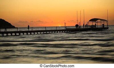 People on pontoon at sunset - People walking on pontoon at...