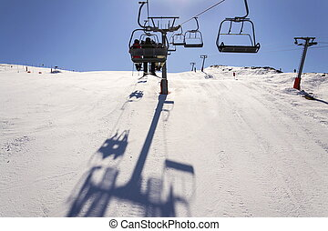 People on ski chair lift in sunny winter Alps, Austria