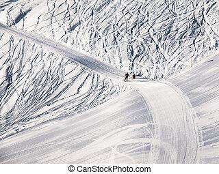 People on ski slope in mountain resort on sunny winter morning