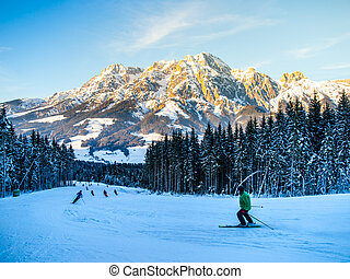People on ski slope in mountain resort on sunny winter morning